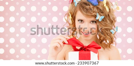 holidays, people and happiness concept - smiling young woman with flowers over pink and white polka dots pattern background - stock photo
