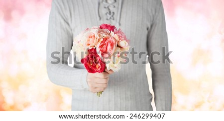holidays, people, feelings and greetings concept - close up of man holding bunch of flowers over pink lights background - stock photo