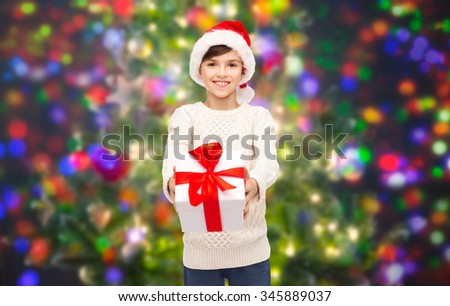holidays, presents, christmas, childhood and people concept - smiling happy boy in santa hat with gift box over lights background - stock photo