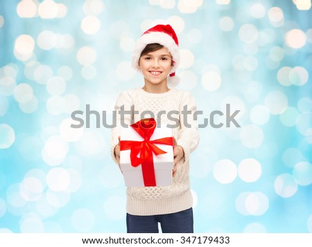 holidays, presents, christmas, childhood and people concept - smiling happy boy in santa hat with gift box over blue holidays lights background - stock photo