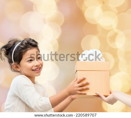 holidays, presents, christmas, childhood and people concept - smiling little girl with gift box over beige lights background - stock photo