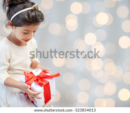 holidays, presents, christmas, childhood and people concept - smiling little girl with gift box over lights background - stock photo