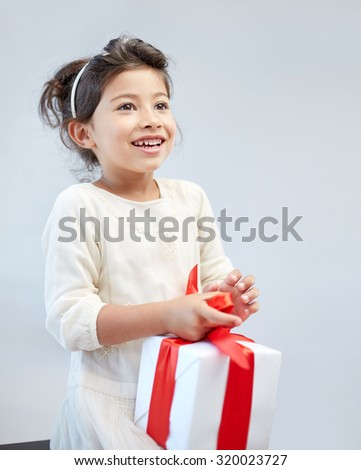 holidays, presents, christmas, childhood and people concept - smiling little girl with gift box at home - stock photo