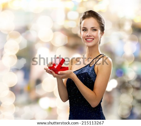 holidays, presents, luxury and happiness concept - smiling woman in dress holding red gift box over lights background - stock photo