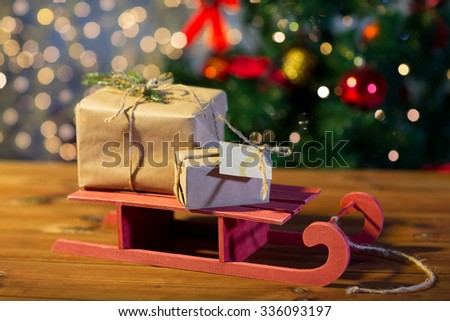 holidays, presents, new year and celebration concept - close up of gift boxes with blank note on red wooden sleigh over christmas tree and lights background - stock photo