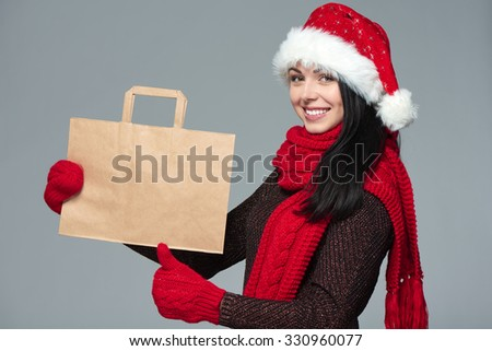 Holidays sale, shopping, Christmas concept. Portrait of smiling woman wearing Santa hat showing shopping bag with empty copy space and gesturing thumb up - stock photo
