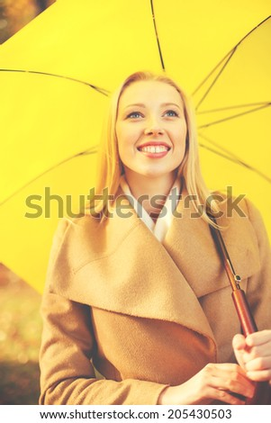 holidays, seasons, travel, tourism, happy people concept - smiling woman with yellow umbrella in the autumn park - stock photo