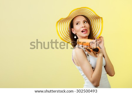 Holidays summer fashion. and skin care concept. Woman in yellow hat holds heart shaped sunglasses sunscreen lotion, bright background copy space - stock photo