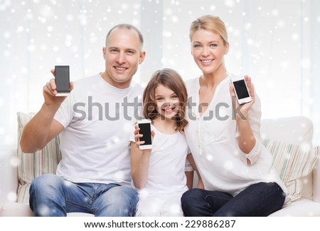 holidays, technology, advertisement and people concept - smiling family showing smartphones blank screens over snowflakes background - stock photo