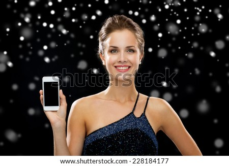 holidays, technology, advertisement and people concept - smiling woman in evening dress showing blank smartphone screen over black snowy background - stock photo