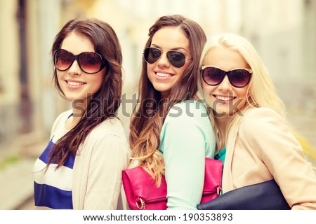 holidays, tourism and happy people concept - three smiling women in sunglasses with bags in the city - stock photo