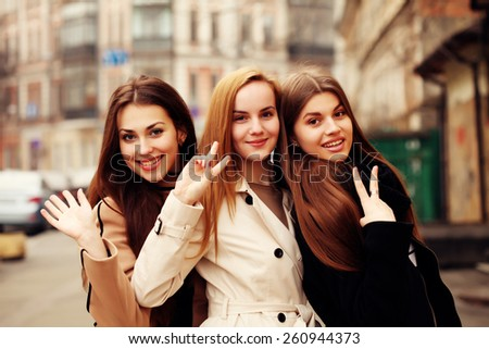 holidays, tourism and happy people concept - three smiling women in the city. Beautiful girls having fun. Outdoors, lifestyle. - stock photo