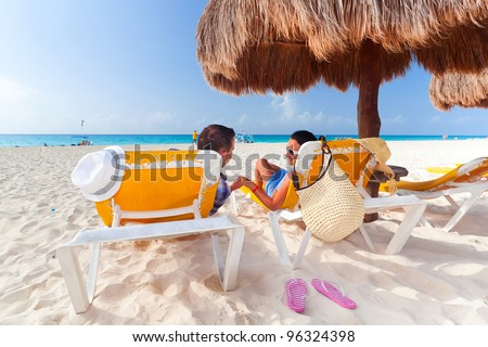 Holidays under parasol at Caribbean Sea - stock photo
