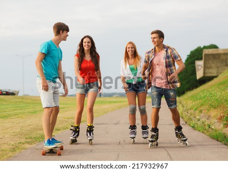 holidays, vacation, love and friendship concept - group of smiling teenagers with roller skates and skateboard riding outdoors - stock photo