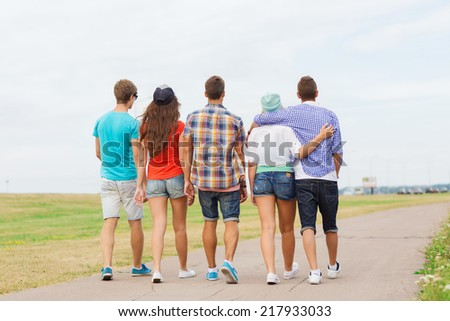 holidays, vacation, love and friendship concept - group of teenagers walking outdoors from back - stock photo