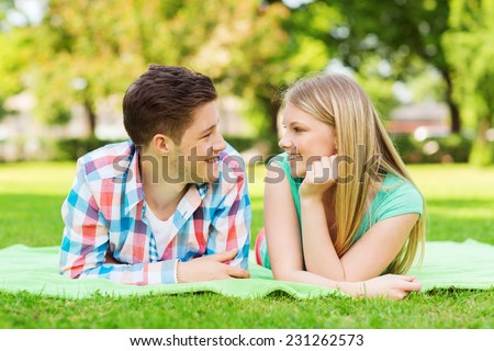 holidays, vacation, love and friendship concept - smiling couple lying on blanket and looking at each other in park - stock photo