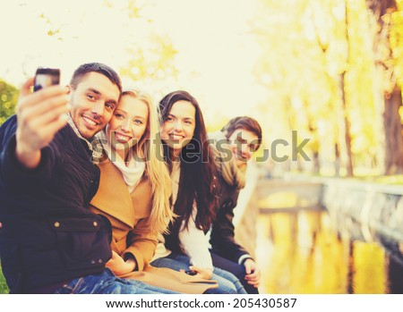 holidays, vacation, travel and tourism concept - group of friends or couples having fun in autumn park and taking selfie - stock photo