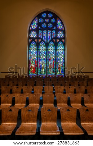 HOLLAND, MICHIGAN - MAY 13: Stained glass window above wooden chairs in the Dimnent Memorial Chapel on the campus of Hope College on May 13, 2015 in Holland, Michigan - stock photo