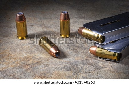 Hollow point handgun ammunition with a pair of steel magazines - stock photo