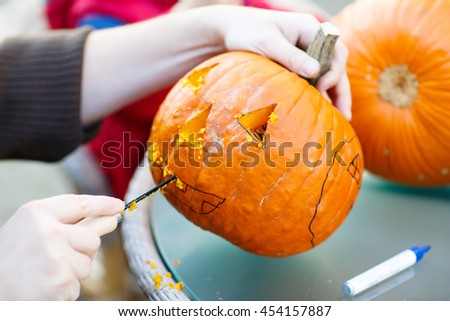 Hollowing out a scary pumpkin to prepare halloween lantern. Jack-o-lantern. Hands with knife and feld pen - stock photo
