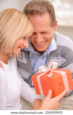 Holly love. Happy agreeable adult smiling couple holding present and sitting on the settee while bonding to each other - stock photo