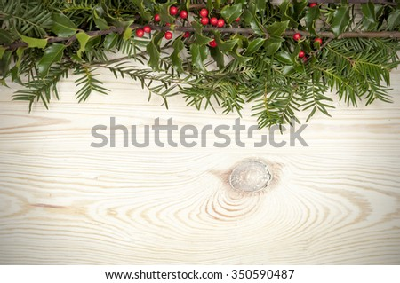 holly on a wooden table - stock photo