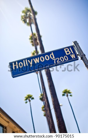 Hollywood boulevard sign, with palm trees in the background - stock photo