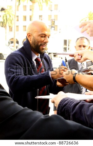 HOLLYWOOD, CA - NOVEMBER 13: Rapper Common is signing posters outside Grauman's Chinese Theatre at the premiere of the movie Happy Feet on November 13, 2011 in Hollywood, CA. - stock photo