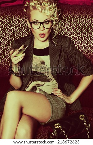 Hollywood celebrity concept. Gorgeous young superstar drinking cocktail disturbed by paparazzi in the night club (lounge bar). Luxurious look and accessories. Hipster style. Indoor shot - stock photo