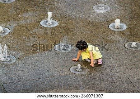 Hollywood & Highland Center, Hollywood, California - February 08 : Child playing in the water fountains, February 08 2015 in the Hollywood & Highland Center, Hollywood, California. - stock photo