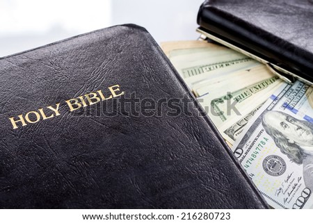 Holy Bible and money. Black wallet - stock photo