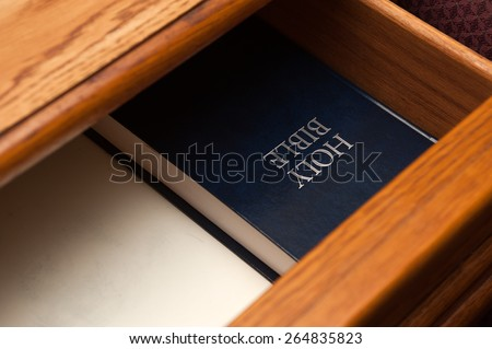Holy Bible book lying in a open drawer. selective focus on a holy bible sign - stock photo