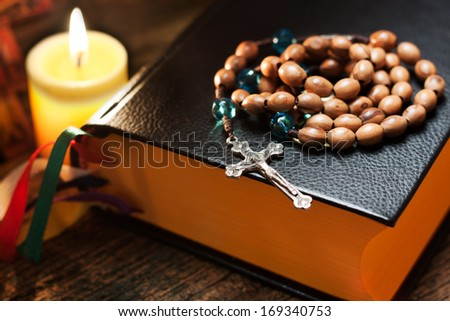 Holy bible with rosary beads on wooden background. Thin depth of field, focus on cross - stock photo