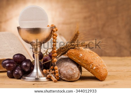 holy communion chalice on wooden table - stock photo