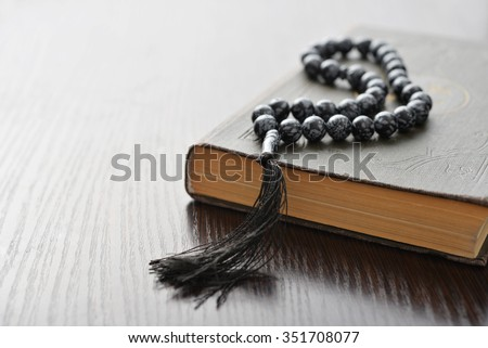 Holy Quran with beads over wooden background closeup. Small shallow DOF. - stock photo