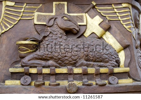 holy sheep statue with gold cross - stock photo