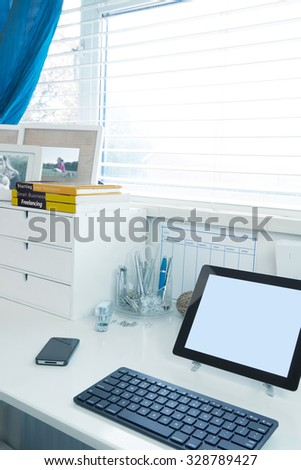 Home and business office interior with a Tablet and phone on the desk - stock photo