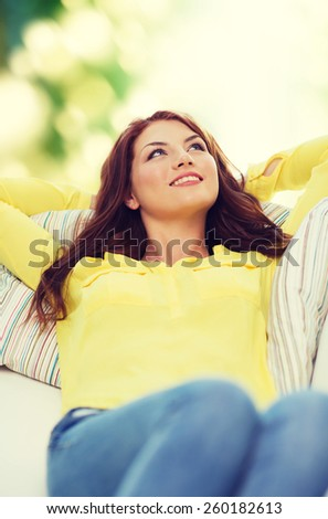 home and happiness concept - smiling young woman lying on sofa at home - stock photo