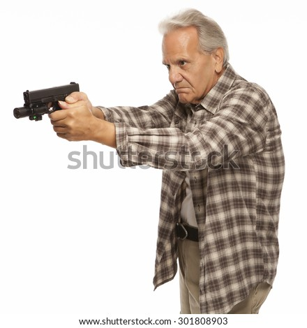 HOME and PERSONAL DEFENSE | Serious adult male with gun and arms extended, ready to shoot. Mature senior with firearm protecting his home or family. - stock photo