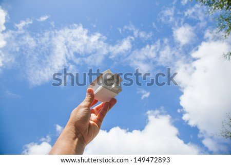Home artificial on the blue sky background. - stock photo