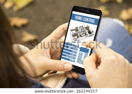 home automation concept: young woman with smart home control app at the park - stock photo