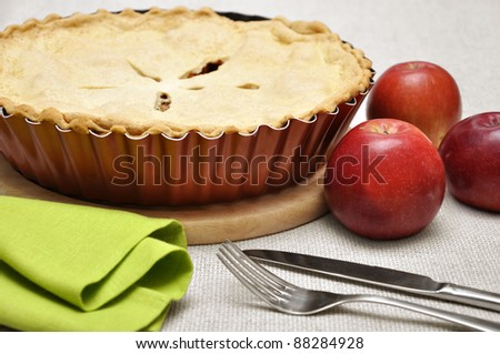 Home-baked apple pie, straight from the oven. Vintage enamel pie plate, fork and knife. - stock photo