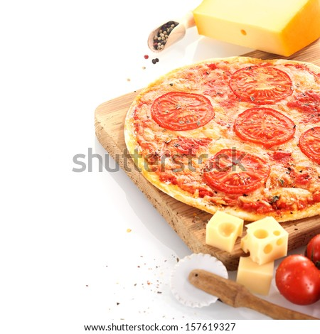 Home baked cheese and tomato pizza surrounded by fresh ingredients and a pizza wheel and served on a wooden board over white - stock photo