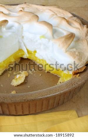 Home-baked lemon meringue pie, in brown pottery pie plate.  One slice missing. - stock photo