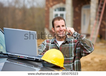 Home: Builder On Cell Phone With Laptop Computer - stock photo