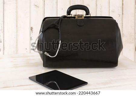 Home call, doctor's bag with stethoscope and Tablet - stock photo