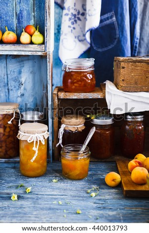 Home canning concept. Fruits Jams preserve on a wooden shelves. Country blue style. - stock photo