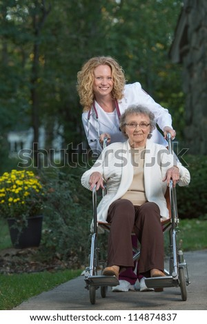 Home Care Nurse Push Senior on Wheelchair in Early Morning Outside House - stock photo