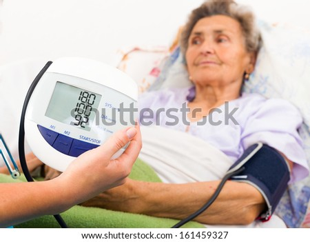 Home care nurse using digital blood pressure measure. - stock photo