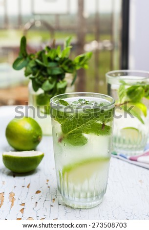 Home chilled lemonade with fresh lime, lemon and mint with honey and ice - stock photo